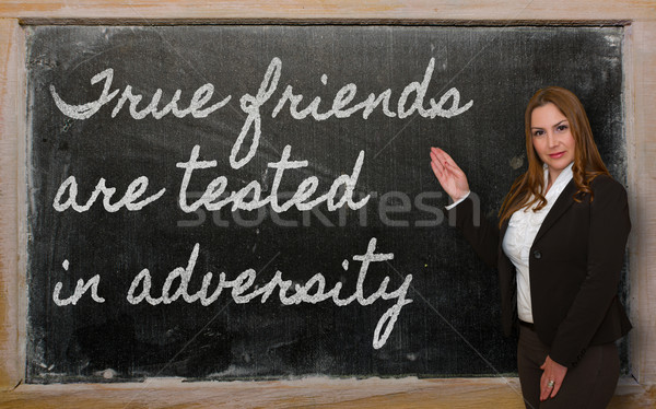 Teacher showing True friends are tested in adversity on blackboa Stock photo © vepar5