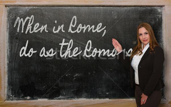 Teacher showing When in Rome, do as the Romans do on blackboard Stock photo © vepar5