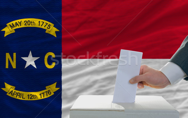 man voting on elections in front of flag US state flag of north  Stock photo © vepar5