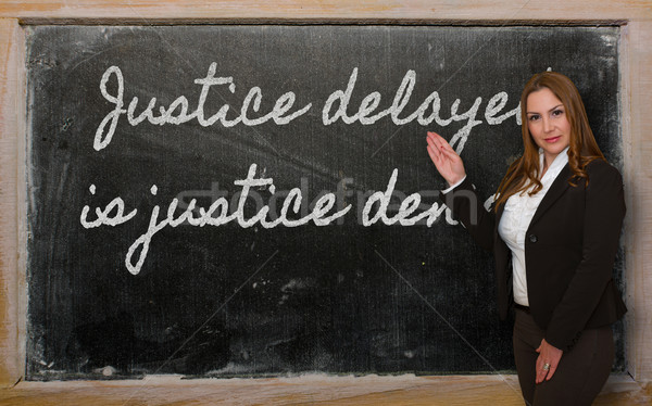 Teacher showing Justice delayed is justice denied on blackboard Stock photo © vepar5
