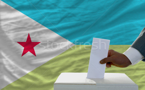 man voting on elections in front of national flag of djibuti Stock photo © vepar5