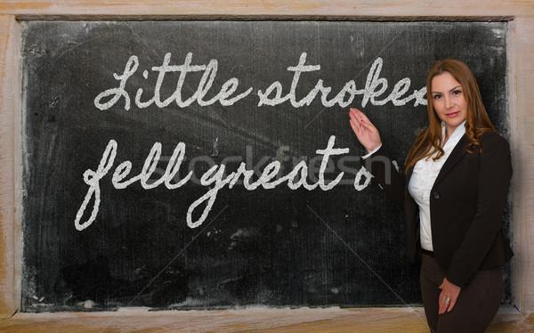 Teacher showing Little strokes fell great oaks on blackboard Stock photo © vepar5