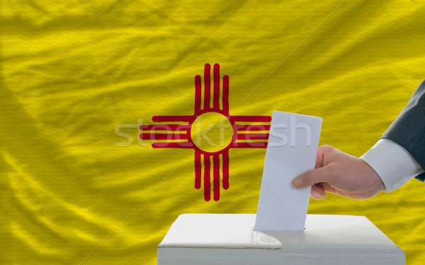 Stock photo: man voting on elections in front of flag US state flag of new me