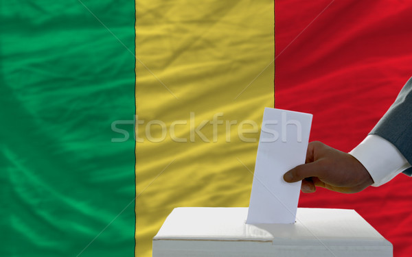 man voting on elections in front of national flag of mali Stock photo © vepar5