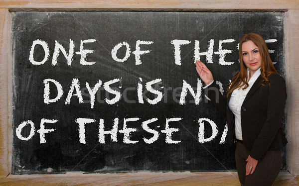 Teacher showing One of these days is none of these days on black Stock photo © vepar5
