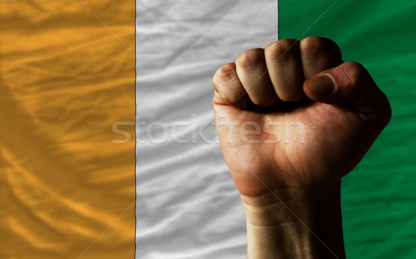 Hard fist in front of ivory coast flag symbolizing power Stock photo © vepar5
