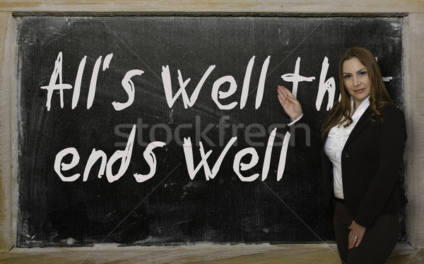 Teacher showing All's well that ends well on blackboard Stock photo © vepar5