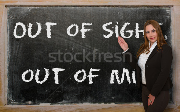 Teacher showing Out of sight, out of mind on blackboard Stock photo © vepar5