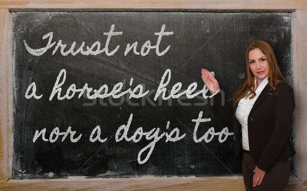 Teacher showing Trust not a horse s heel nor a dog's tooth on bl Stock photo © vepar5