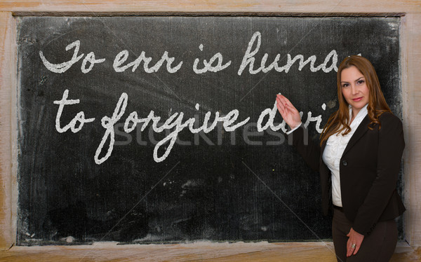 Teacher showing To err is human, to forgive divine on blackboard Stock photo © vepar5
