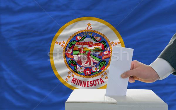 Foto stock: Homem · votação · eleições · bandeira · cédula · caixa