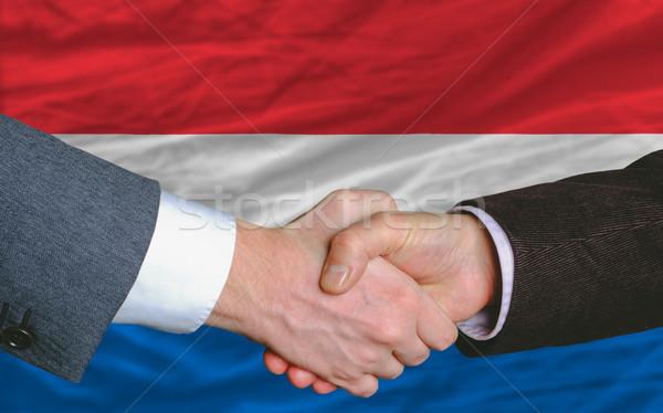 Stock photo: businessmen handshake after good deal in front of netherlands fl