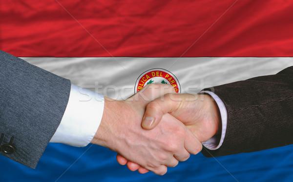 businessmen handshake after good deal in front of paraguay flag Stock photo © vepar5