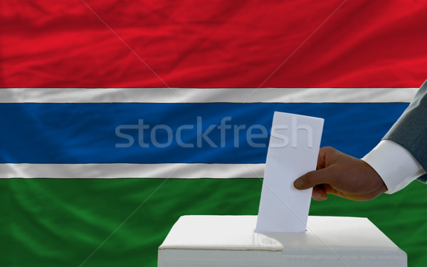 man voting on elections in front of national flag of gambia Stock photo © vepar5