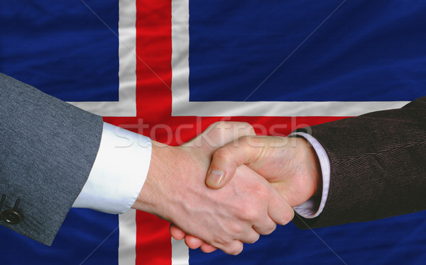 Businessmen Handshake After Good Deal In Front Of Iceland Flag