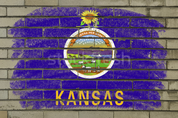Stock photo: grunge flag of US state of kansas on brick wall painted with cha