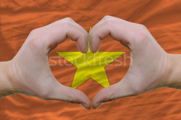 Heart and love gesture showed by hands over flag of vietnam back Stock photo © vepar5
