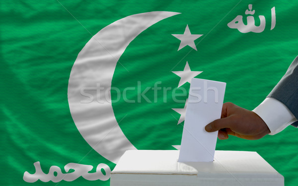 man voting on elections in front of national flag of comoros Stock photo © vepar5