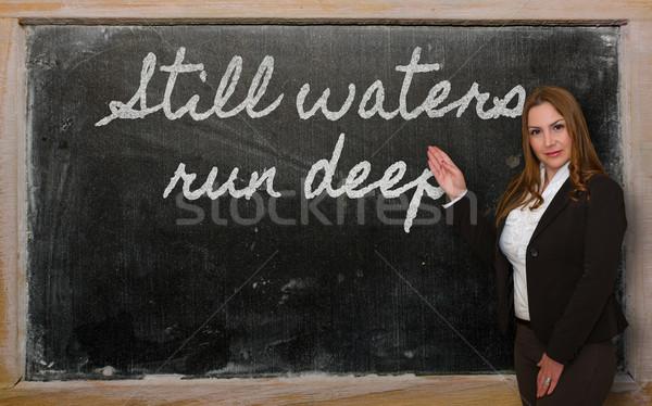 Teacher showing Still waters run deep on blackboard Stock photo © vepar5