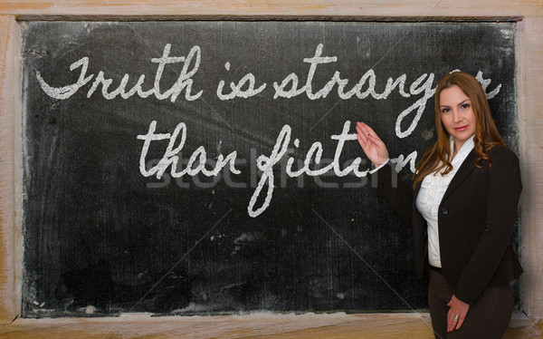 Teacher showing Truth is stranger than fiction on blackboard Stock photo © vepar5