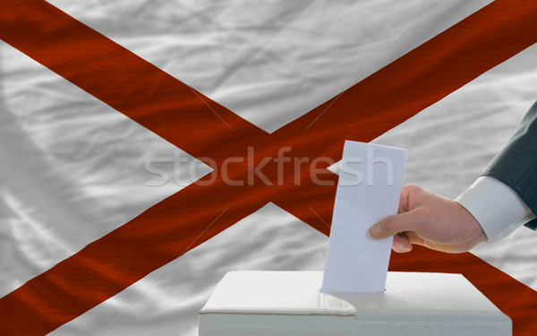 man voting on elections in front of flag US state flag of alabam Stock photo © vepar5