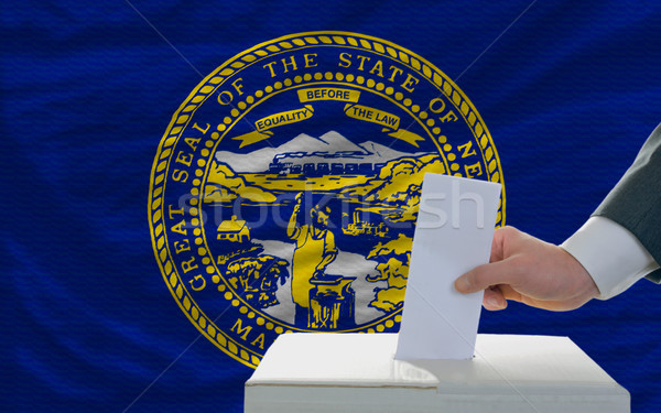 man voting on elections in front of flag US state flag of nebras Stock photo © vepar5