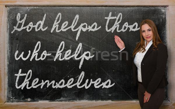 Teacher showing God helps those who help themselves on blackboar Stock photo © vepar5
