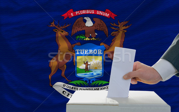 man voting on elections in front of flag US state flag of michig Stock photo © vepar5
