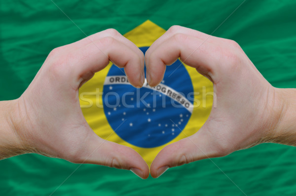 Stock photo: Heart and love gesture showed by hands over flag of brazil backg