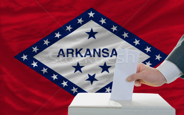 man voting on elections in front of flag US state flag of arkans Stock photo © vepar5