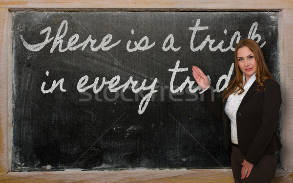 Teacher showing There is a trick in every trade on blackboard Stock photo © vepar5