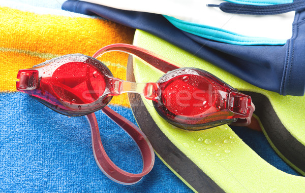 Wet swimming goggles and towel Stock photo © veralub