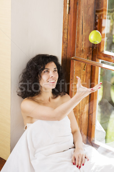 Woman throws up apple on wooden sill Stock photo © vetdoctor