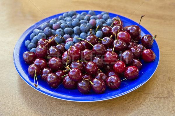 Blueberries and cherries lay on blue plate Stock photo © vetdoctor