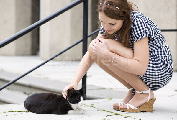Woman in checkered dress fondle street cat Stock photo © vetdoctor