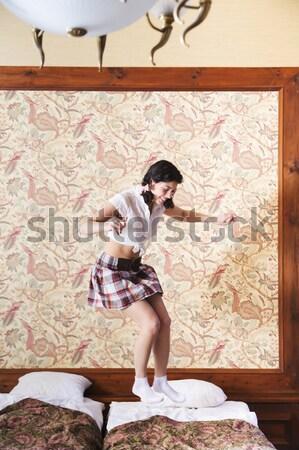 Woman in schoolgirl dress jump on bed Stock photo © vetdoctor