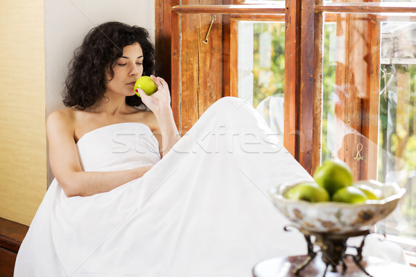 Woman smells green apple on wooden sill Stock photo © vetdoctor