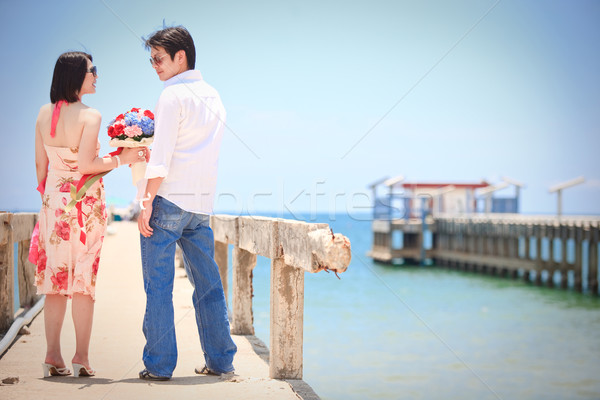 couples make eye contact at pier on the beach Stock photo © vichie81