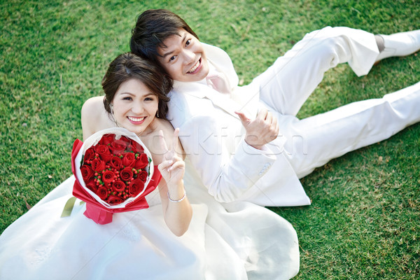 portrait of bride and groom sitting on fresh grass with rose bou Stock photo © vichie81
