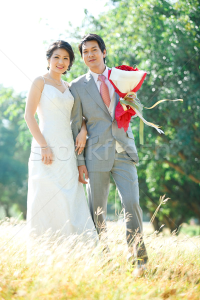 couples of bride and groom standing over meadows field Stock photo © vichie81