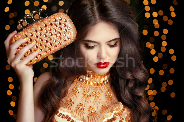 Elegant fashion brunette woman in gold. Wavy hair style. Red lip Stock photo © Victoria_Andreas