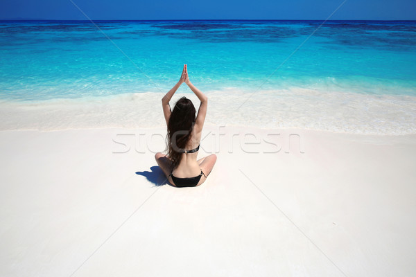 Young woman practicing yoga on the tropical beach with blue wate Stock photo © Victoria_Andreas