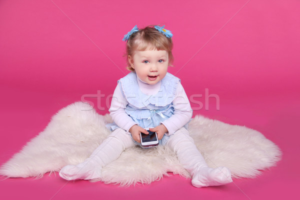 Funny little girl playing with mobile phone over pink background Stock photo © Victoria_Andreas