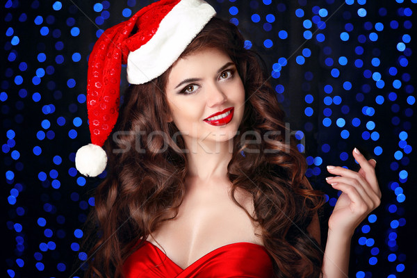 Stock photo: Beautiful happy smiling girl in santa hat with red lips, hand ho