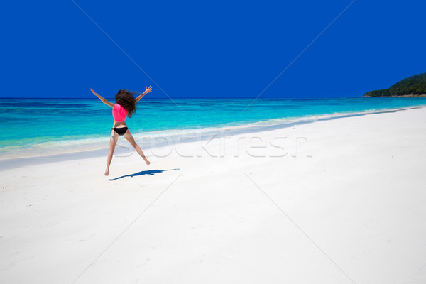 Enjoying life. Happy woman jumping on exotic sea. Fit brunette g Stock photo © Victoria_Andreas