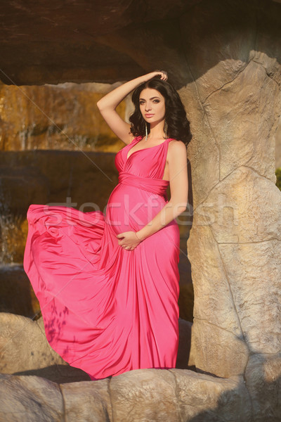 Beautiful pregnant woman wearing in blowing pink dress posing ag Stock photo © Victoria_Andreas