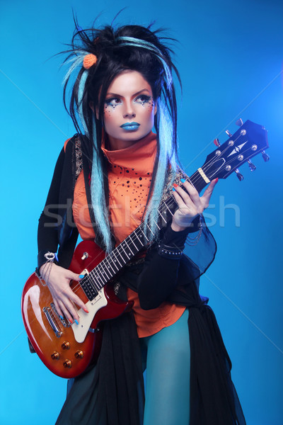 Rock girl plating on electric guitar isolated on blue background Stock photo © Victoria_Andreas