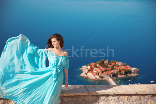 Enjoyment. Fashion smiling woman with blowing dress over blue sk Stock photo © Victoria_Andreas