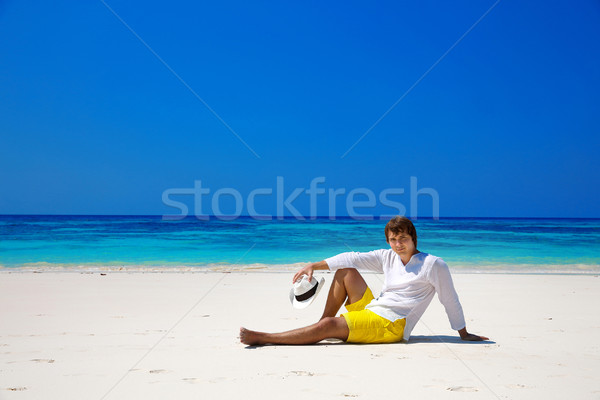 Successful handsome man in hat resting on exotic seashore with b Stock photo © Victoria_Andreas