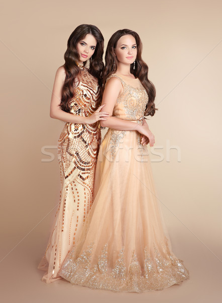 Two fashion ladies. Beautiful women with wavy hair wears in long Stock photo © Victoria_Andreas